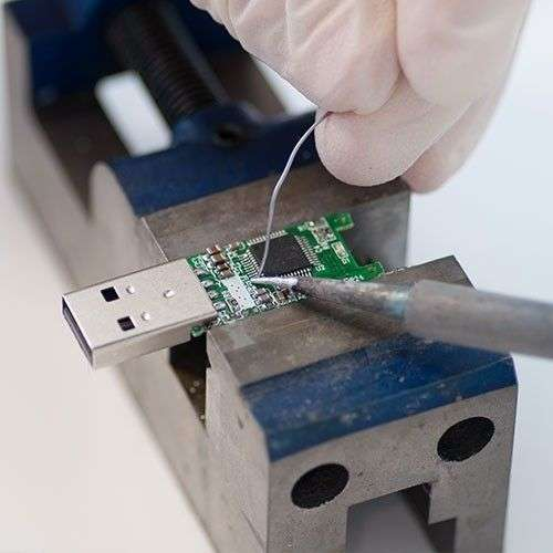 Close up on a USB drive being repaired by a technician